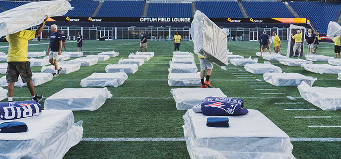 Volunteers set up the 200 beds on the field at Gillette Stadium.