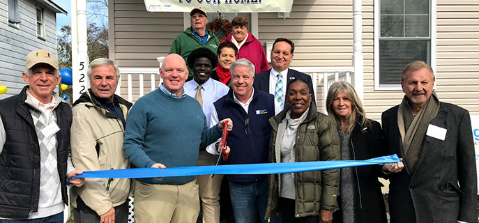 Representatives from Bob's Discount Furniture and the New York Giants help cut the ribbon on the new Rights of Passage II home in Asbury Park, New Jersey.